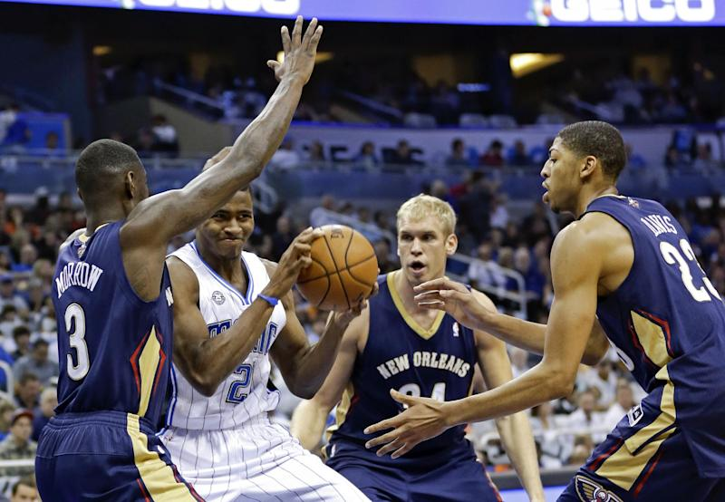 Orlando Magic's Maurice Harkless, second from left, tries to pass the ball as he finds himself pressured by New Orleans Pelicans' Anthony Morrow (3), Greg Stiemsma, center, and Anthony Davis during the first half of an NBA basketball game in Orlando, Fla., Friday, Nov. 1, 2013. (AP Photo/John Raoux)