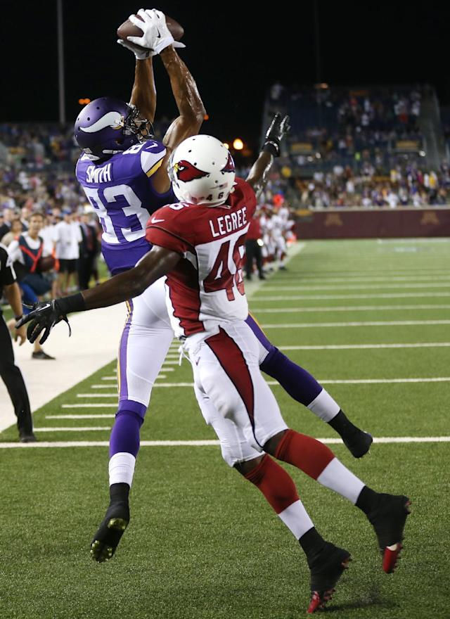 Minnesota Vikings wide receiver Rodney Smith, left, catches a 2-yard touchdown pass over Arizona Cardinals defensive back Jimmy Legree during the second half of an NFL preseason football game, Saturday, Aug. 16, 2014, in Minneapolis. The Vikings won 30-28. (AP Photo/Jim Mone)