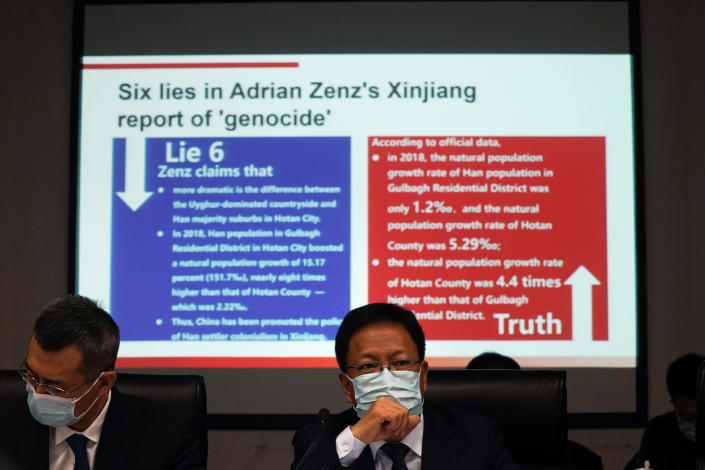 """Xu Guixiang, a deputy spokesperson for the Xinjiang regional government, wears mask near a slide refuting claims of genocide during a press conference in Beijing, China. The Chinese official on Monday denied Beijing has imposed coercive birth control measures among Muslim minority women, following an outcry over a tweet by the Chinese Embassy in Washington claiming that government polices had freed women of the Uighur ethnic group from being """"baby-making machines."""" (AP Photo/Ng Han Guan)"""