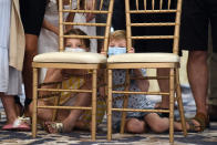 Children sit behind chairs as they wait to watch President Donald Trump speak at Trump National Golf Club Bedminster in Bedminster, N.J., Friday, Aug. 7, 2020. (AP Photo/Susan Walsh)