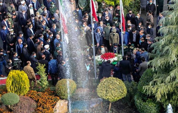 Iranian officials pray over the coffin of top nuclear scientist Mohsen Fakhrizadeh during his funeral in Tehran on Monday, in this picture provided by the country's defence ministry