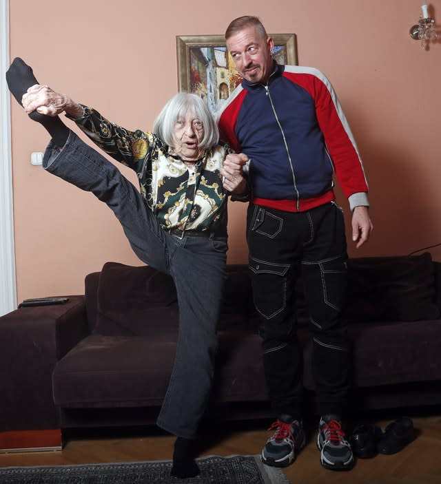 Agnes Keleti, former Olympic gold medal winning gymnast, demonstrates her flexibility as she poses for a photo with her son Rafael at her apartment in Budapest, Hungary