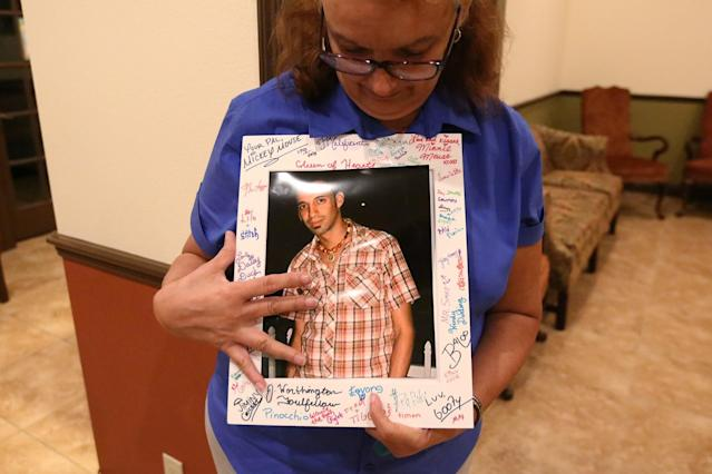 <p>Maria de los Angeles, the mother of Eric Ivan Ortiz-Rivera, one of the victims of the shooting at the Pulse night club in Orlando, displays a photo of her son at his wake in Kissimmee, Florida, on June 16, 2016. (Photo: Carlo Allegri/Reuters) </p>