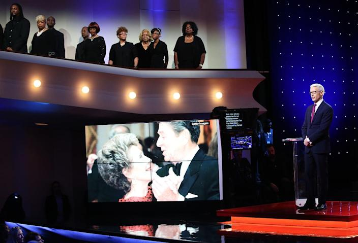 <p>Moderator Anderson Cooper observes a moment of silence for Nancy Reagan on Sunday prior to the CNN Democratic presidential primary debate between Hillary Clinton and Bernie Sanders at the Whiting Auditorium in Flint, Mich.<i> (Photo: Scott Olson/Getty Images)</i></p>