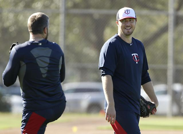 Minnesota Twins pitchers Phil Hughes, right, and Glen Perkins, left, talk on the field during spring training baseball practice on Sunday, Feb. 16, 2014, in Fort Myers, Fla. (AP Photo/Steven Senne)