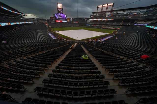 A few fans sit under umbrellas in the rain during a delayed baseball game between the Colorado Rockies and the New York Mets, Tuesday, June 19, 2018, in Denver. (AP Photo/Jack Dempsey)