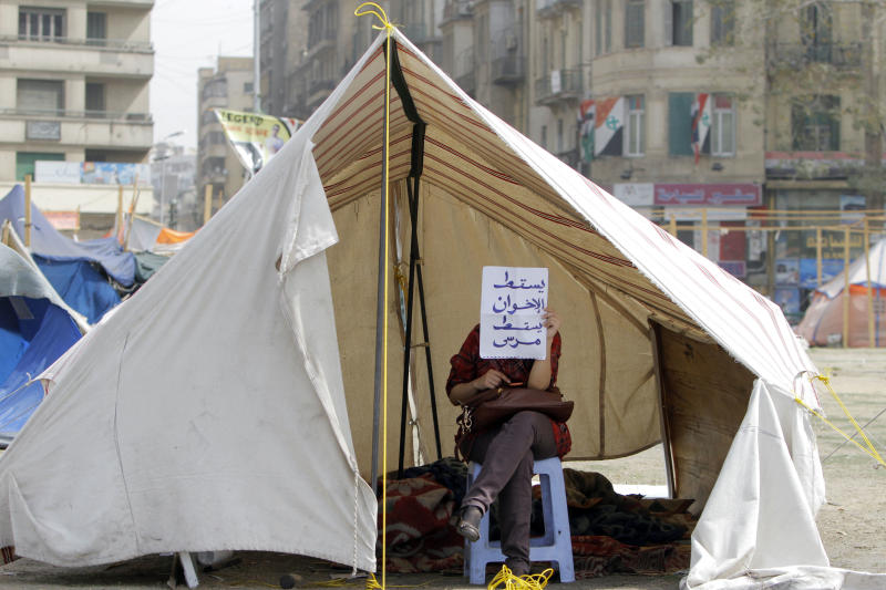 "An Egyptian activist holds a piece of paper with Arabic that reads, ""down with the Muslim Brotherhood, down with Morsi,"" in a tent in Tahrir Square, the focal point of the Egyptian revolution, in Cairo, Egypt, Sunday, March 3, 2013. Security forces re-opened Tahrir Square removing barbed wire across the entrances to allow traffic to flow normally for the first time in months. Protesters have held a sit-in in the square since Nov. 22, 2013 after President Morsi issued a controversial constitutional declaration that rendered his decisions above judicial supervision. (AP Photo/Amr Nabil)"
