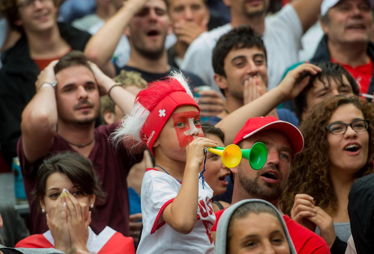 Swiss soccer fans show their emotions during the live broadcast of the Brazil Soccer FIFA World Cup match between Switzerland and Argentina at the public viewing zone on the Piazza Manzoni in Lugano, Switzerland, Monday, July 1 2014. (AP Photo/Keystone, Gabriele Putzu)