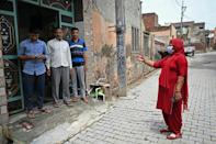 A health worker (R) speaks to a family during a vaccine awareness campaign in Kalwa village, Haryana state