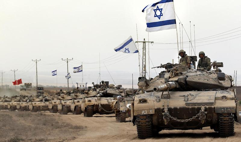 Israeli tanks drive near the border between Israel and the Gaza Strip as they return from the Hamas-controlled Palestinian coastal enclave on August 5, 2014