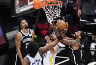 Golden State Warriors center James Wiseman (33) and guard Stephen Curry try to interrupt a shot by Brooklyn Nets guard Kyrie Irving (11) during the second quarter of an NBA basketball game Tuesday, Dec. 22, 2020, in New York. (AP Photo/Kathy Willens)