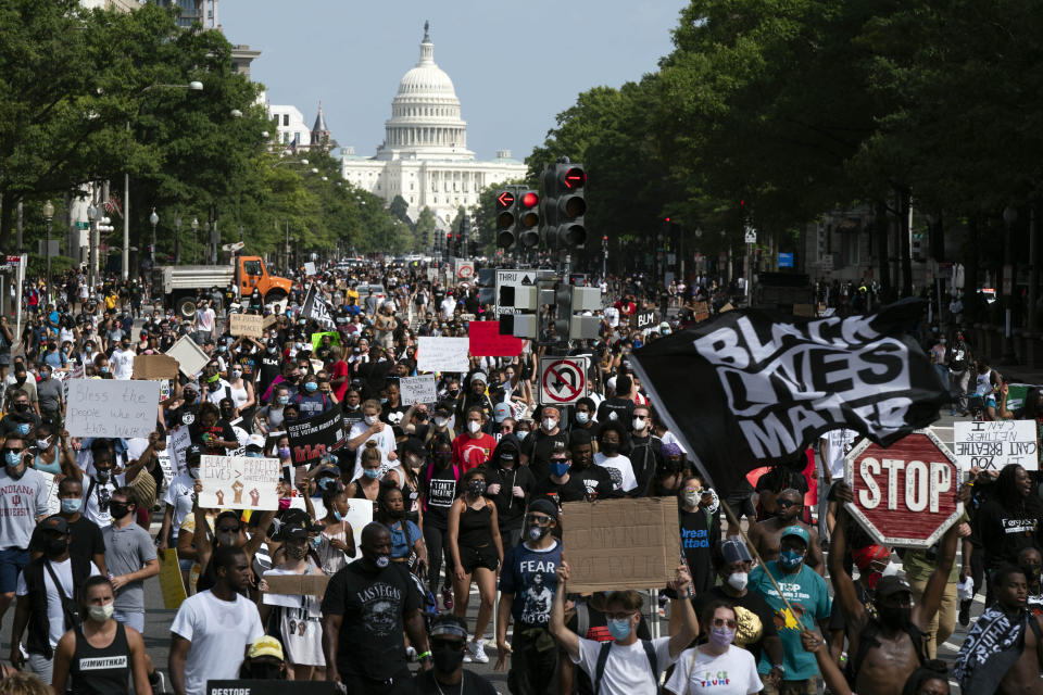 """FILE - In this Aug. 28, 2020, file photo, people walk on Pennsylvania Avenue during the March on Washington, on the 57th anniversary of the Rev. Martin Luther King Jr.'s """"I Have A Dream"""" speech. In the nation's capital on Saturday, Aug. 28, 2021, multiracial coalitions of civil, human and labor rights leaders are convening rallies and marches to urge passage of federal voter protections that have been eroded since the Voting Rights Act of 1965. (AP Photo/Jose Luis Magana, File)"""