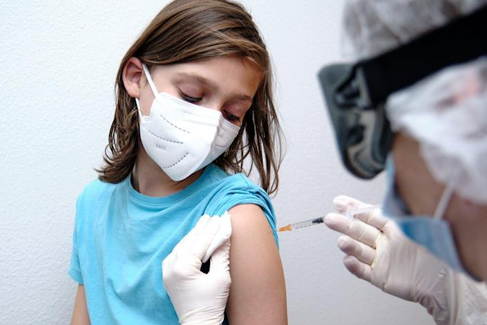 Female doctor giving covid-19 vaccine to a boy