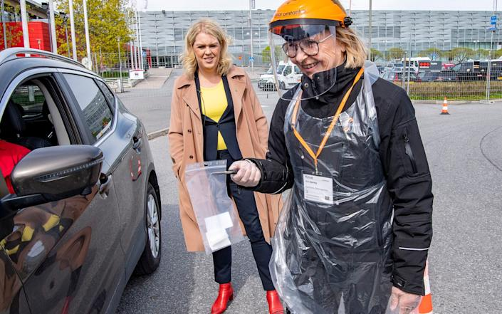 Sweden's Minister for Health and Social Affairs Lena Hallengren, center, looks on as health worker Gun Bjorling administers a Covid-19 test at a drive-in-test station - Jonas Ekstromer /TT NEWS AGENCY