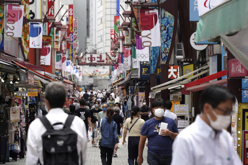 People wearing face masks to help curb the spread of the coronavirus walk across a shopping alley near Ueno Station in Tokyo Friday, July 30, 2021. Japan is set to expand the coronavirus state of emergency in Tokyo to neighboring areas and the western city of Osaka on Friday in the wake of a record-breaking surge in infections while the capital hosts the Olympics. (AP Photo/Kantaro Komiya)