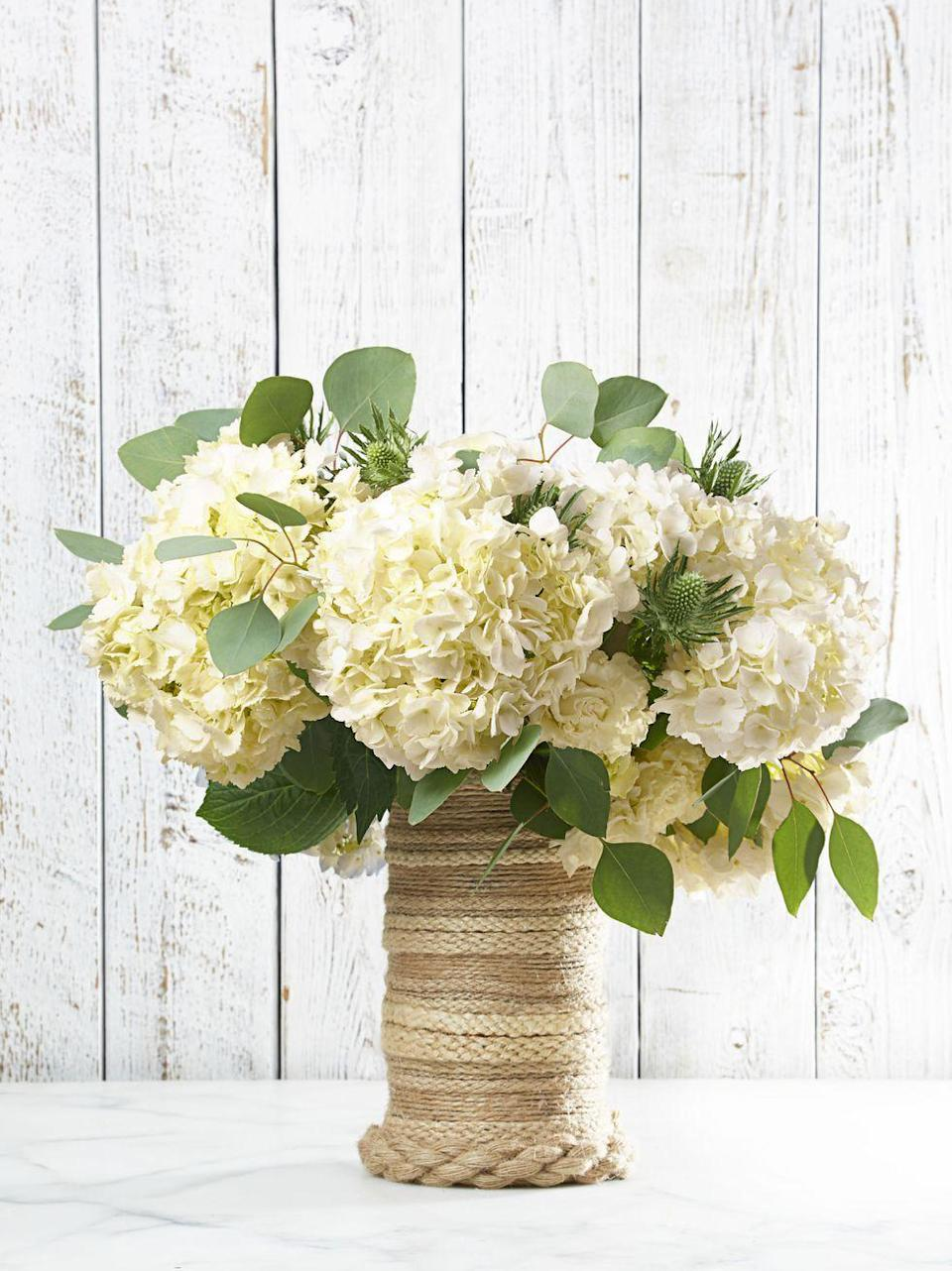 """<p>Give a nod to warm months to come with this elegant rope vase. Pro tip: Flip the vase upside down and work with a hot glue gun from base to mouth. End strands in back so there is a """"seam"""" on only one side. Toss in a beachy bunch of white hydrangeas, and you're ready for a clambake!</p>"""