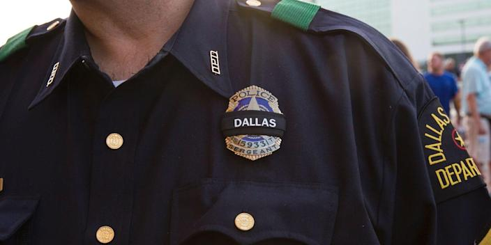"""A Dallas police officer wears a black ribbon over his badge at a """"Dallas Strong"""" candlelight vigil outside City Hall in Dallas, Texas, on July 11, 2016."""