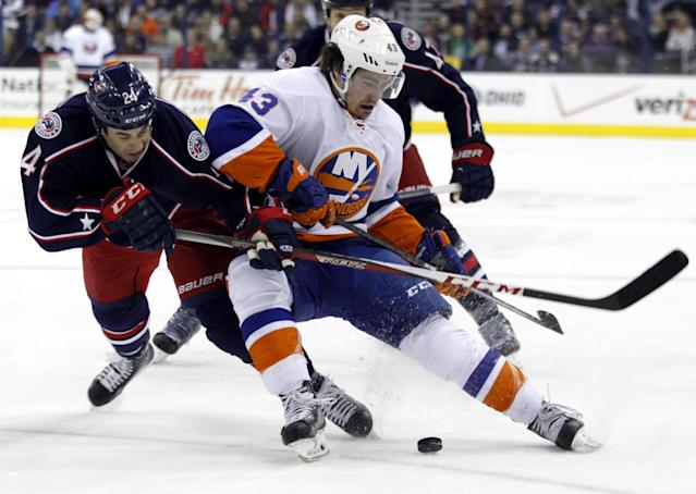 Columbus Blue Jackets' Derek MacKenzie, left, and New York Islanders' Mike Halmo work for the puck in the first period of an NHL hockey game in Columbus, Ohio, Sunday, April 6, 2014. (AP Photo/Paul Vernon)