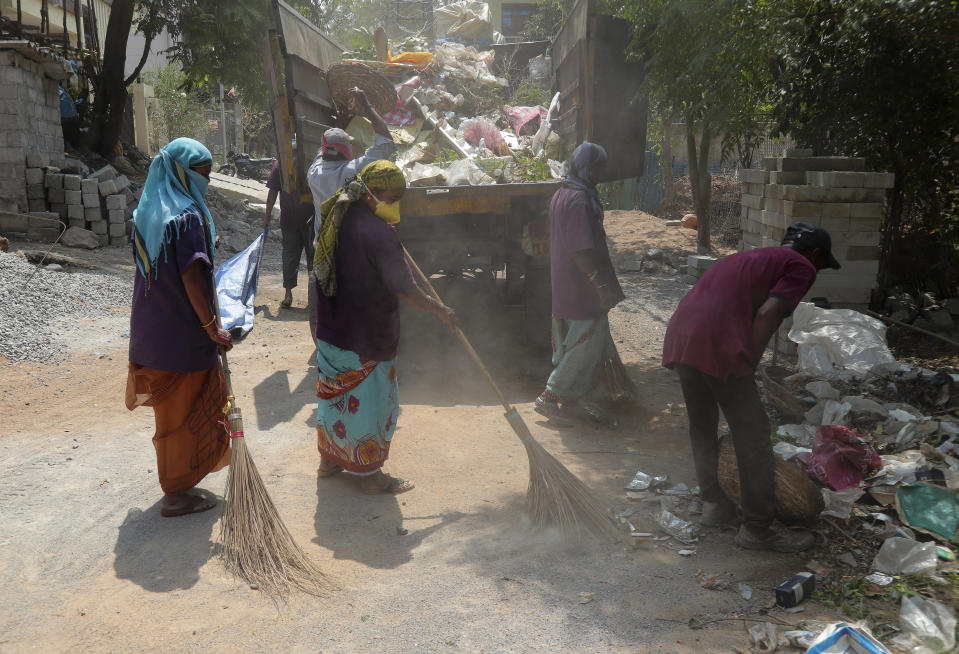Indian municipal workers clean a residential area from where a patient was tested positive for COVID-19 in Hyderabad, India, Wednesday, March 4, 2020. A new virus first detected in China has infected more than 90,000 people globally and caused over 3,100 deaths. The World Health Organization has named the illness COVID-19, referring to its origin late last year and the coronavirus that causes it. (AP Photo/Mahesh Kumar A.)
