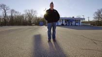 Craig DeOld, commander at Veterans of Foreign War Post #1018, stands in the post's empty parking lot as the sun sets, Monday, March 15, 2021, in Boston. Local bars and halls run by VFW and American Legion posts have fallen on hard times during the coronavirus pandemic. Organizers say many risk permanent closure after states ordered them, like other bars and halls, to shutter last spring. (AP Photo/Charles Krupa)