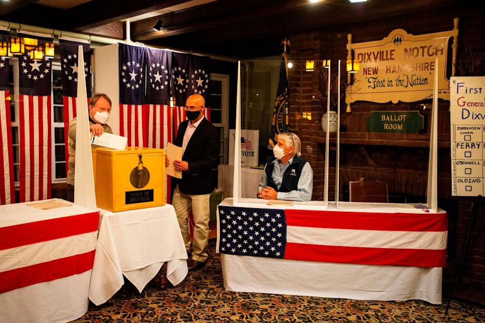 Tom Tillotson drops voters ballots into the ballot box at the Hale House at the historic Balsams Resort during midnight voting as part of the first ballots cast in the United States Presidential Election in Dixville Notch, New Hampshire.