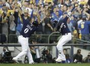 Milwaukee Brewers' Orlando Arcia celebrates his home run with third base coach Ed Sedar during the fifth inning of Game 2 of the National League Championship Series baseball game against the Los Angeles Dodgers Saturday, Oct. 13, 2018, in Milwaukee. (AP Photo/Matt Slocum)