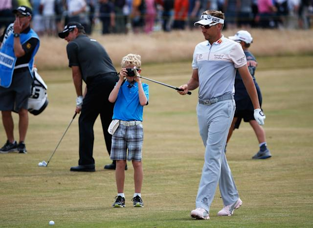 GULLANE, SCOTLAND - JULY 17: Ian Poulter of England walks ahead of son Luke who is taking pictures ahead of the 142nd Open Championship at Muirfield on July 17, 2013 in Gullane, Scotland. (Photo by Rob Carr/Getty Images)