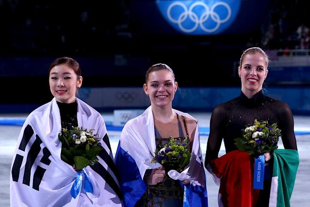 SOCHI, RUSSIA - FEBRUARY 20: (L-R) Silver medalist Yuna Kim of South Korea, gold medalist Adelina Sotnikova of Russia and bronze medalist Carolina Kostner of Italy celebrate during the flower ceremony for the Ladies' Figure Skating on day 13 of the Sochi 2014 Winter Olympics at Iceberg Skating Palace on February 20, 2014 in Sochi, Russia. (Photo by Ryan Pierse/Getty Images)