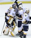 Teammates congratulate Nashville Predators goalie Pekka Rinne (35), of Finland, after their 3-2 win over the Detroit Red Wings in Game 3 of an NHL hockey Stanley Cup first-round playoff series in Detroit, Sunday, April 15, 2012. (AP Photo/Carlos Osorio)