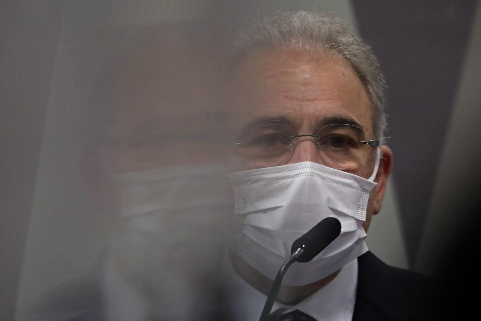 Brazil's Health Minister Marcelo Queiroga, whose image is reflected on the left on a protective virus shield, testifies before the Senate in an investigation of the government's management of the COVID-19 pandemic, in Brasilia, Brazil, Tuesday, June 8, 2021. (AP Photo/Eraldo Peres)
