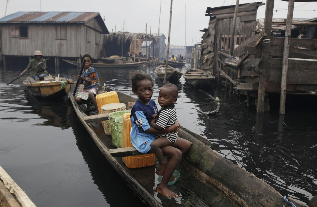 In this photo taken Thursday, July 26, 2012, a woman paddles a canoe past stilt houses at Makoko in Lagos, Nigeria. The teeming, floating Makoko slum rises out of the murky lagoon water that separates mainland Nigeria from the island that gave birth to its largest city, a permanent haze of smoke rising from its homes built on timber stilts. A government-led eviction last week that saw men in speedboats destroy homes with machetes there left about 3,000 people homeless and raised new fears among activists that authorities may try to wipe it out the area entirely. (AP Photo/Sunday Alamba)