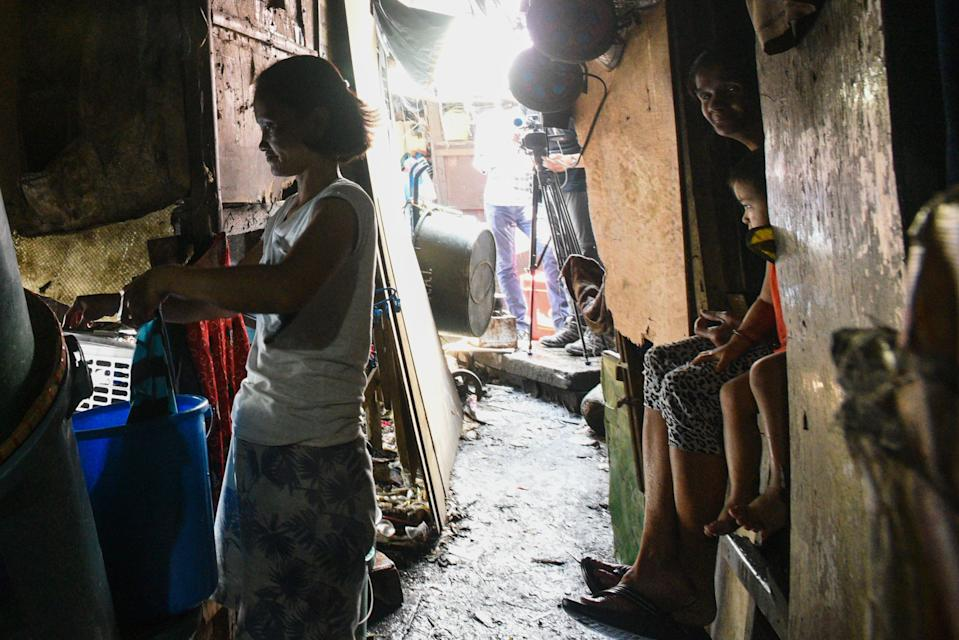 TOPSHOT - This photo taken on March 18, 2020 shows a mother washing her laundry outside her home along the river in Manila. - Asian nations have imposed increasingly heavy measures to fight the outbreak of the COVID-19 coronavirus, the Philippines has ordered half its population of some 110 million to stay home. (Photo by Maria TAN / AFP) / TO GO WITH Health-virus-Philippines-poverty,FOCUS by Joshua Melvin and Ron Lopez (Photo by MARIA TAN/AFP via Getty Images)