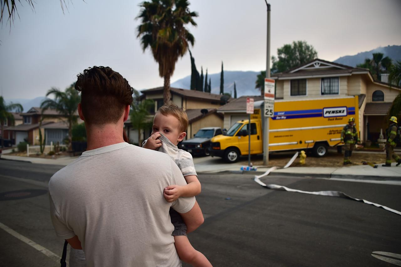 <p>A toddler covers his nose at the Holy Fire in Lake Elsinore, California, southeast of Los Angeles on Aug. 10, 2018. (Photo: Robyn Beck/AFP/Getty Images) </p>