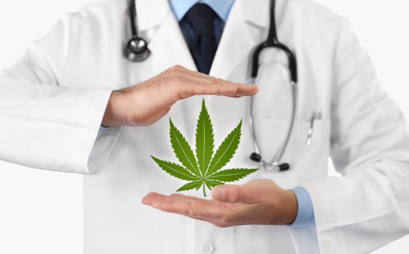 A physician with a stethoscope who has a suspended cannabis leaf between his hands.
