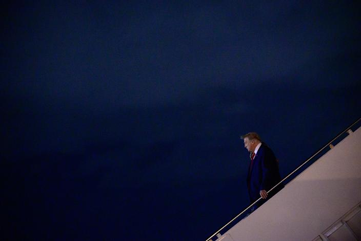 President Donald Trump and first lady Melania Trump depart Air Force One after arriving in West Palm Beach, Fla., Dec. 23, 2020. (Erin Scott/The New York Times)