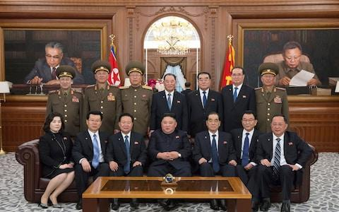 Kim Jong-un poses in a photo with newly-elected members of the leadership bodies of the state at the headquarters building of the Party Central Committee in Pyongyang - Credit: AFP