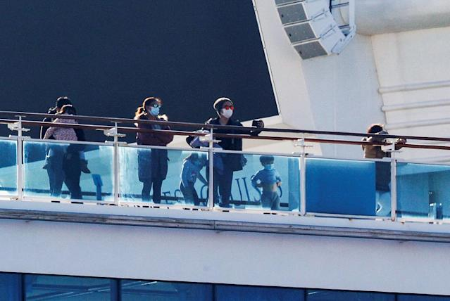 Passengers and children stand on the deck of the cruise ship Diamond Princess, as the vessel's passengers continue to be tested for coronavirus (Reuters)
