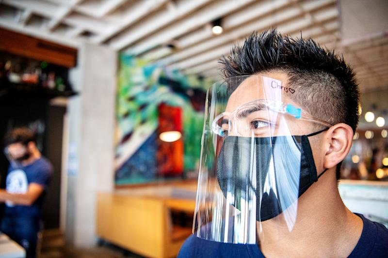 Christopher Gonzalez, along with other employees at Guerrilla Taco, wears protective gear.