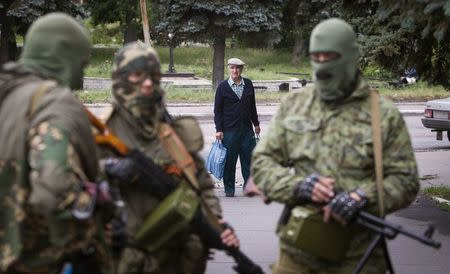 A man looks at armed pro-Russian separatists at a town center in Snizhnye in eastern Ukraine June 12, 2014. REUTERS/Shamil Zhumatov
