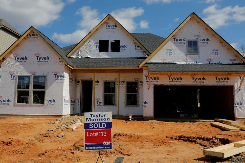 """FILE PHOTO: A home under construction stands behind a """"sold"""" sign in a new development in York County, South Carolina"""