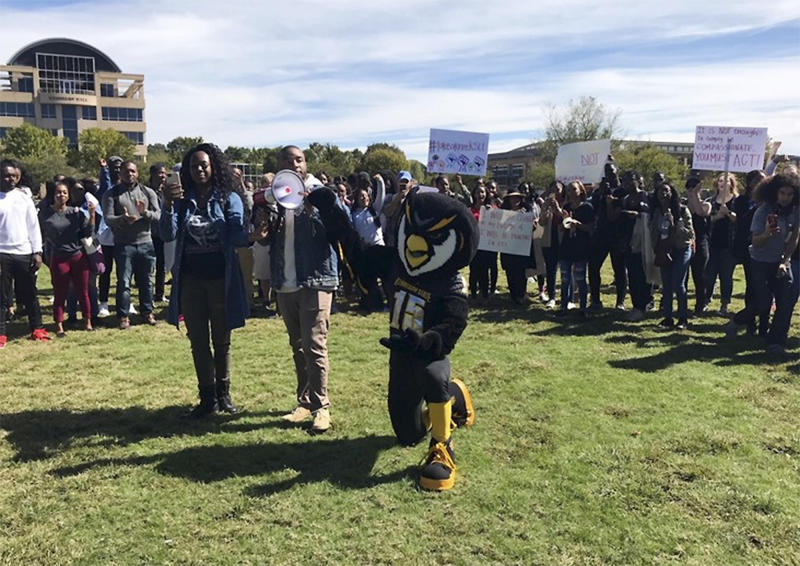 In October, Kennesaw State University students and faculty, along with Kenneth Sturkey, who dresses as the university's mascot Scrappy the Owl, rally in support of five cheerleaders who knelt during the national anthem. (AP)