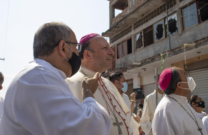 Monsignor Franco Coppola, the Vatican's diplomat to Mexico, looks at broken windows upon arrival to Aguililla, a town that has been cut off by warring cartels in Michoacan state, Mexico, Friday, April 23, 2021, where he will meet families and celebrate Mass. State police and soldiers were sent in to restore order earlier this month, but cartels responded by parking hijacked trucks across roads to block them, as well as digging deep trenches across roadways. (AP Photo/Armando Solis)