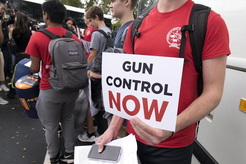 Proitest: Students from Marjory Stoneman Douglas High School hold signs while waiting to board buses in Parkland, Florida (EPA)