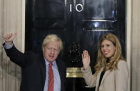 In this Friday, Dec. 13, 2019, file photo, Britain's Prime Minister Boris Johnson and his partner Carrie Symonds wave from the steps of number 10 Downing Street in London. U.K. newspapers are reporting that Prime Minister Johnson and his fiancée Symonds married Saturday, May 29, 2021, in a small private ceremony in London. The Mail on Sunday and the Sun said the couple wed at the Roman Catholic Westminster Cathedral in front of a small group of friends and family. (AP Photo/Matt Dunham, File)