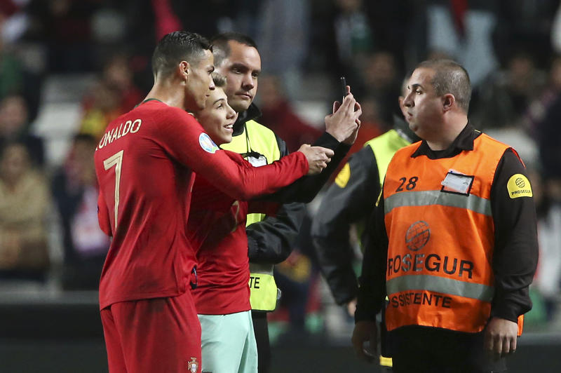 Portugal's Cristiano Ronaldo, left, takes a selfie with a young fan at the end of the Euro 2020 group B qualifying soccer match between Portugal and Ukraine at the Luz stadium in Lisbon, Friday, March 22, 2019. (AP Photo/Armando Franca)