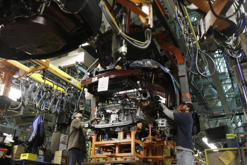 In this Wednesday, Dec. 1, 2010, file photo, plant employees put an engine block in a 2011 Ford Explorer on the assembly line at Ford's Chicago Assembly Plant, in Chicago. The plant is one 13 North American factories where Ford Motor Co. will be adding a a week of production in 2012,  so the company can make another 40,000 vehicles this year and meet the needs of rising car and truck sales. (AP Photo/M. Spencer Green)
