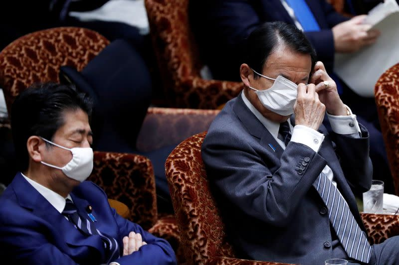 Japan's Finance Minister Taro Aso adjusts his protective face mask during an upper house parliamentary session in Tokyo