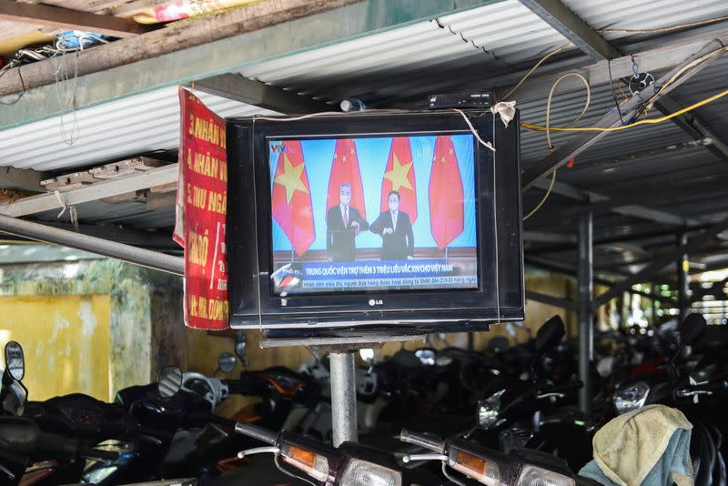A television displays news about Chinese foreign minister Wang Yi's visit to Vietnam, at a street in Hanoi