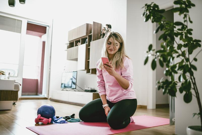 Fit Female Stretching At Home On Exercise Mat And Taking Selfie On Smartphone