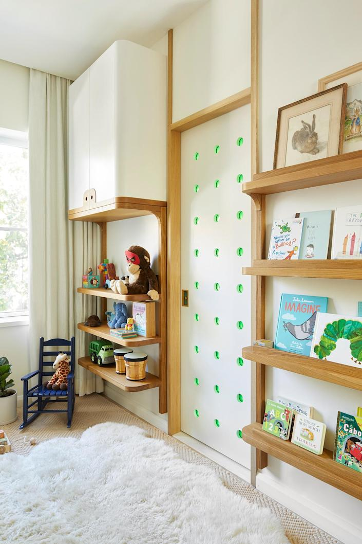 Here in the kids' room, the custom millwork was designed by the architects and fabricated by Tony Sandkamp. The custom door with green glass circles was designed by the architects as well and leads into the bathroom.